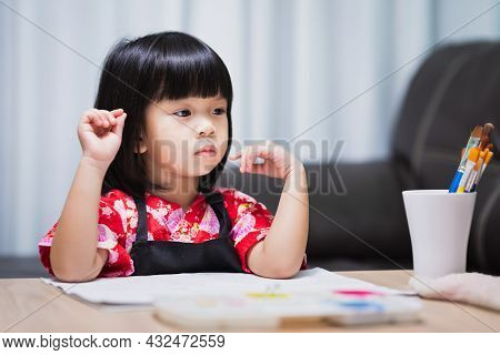 Asian Girl Sits And Thinks, Imagining The Topic Of Art That Will Be Done Today. Child Are Sitting Ga
