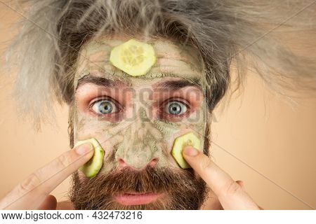 Close Up Funny Man With Clay Mask And Cucumber Slices On Face. Male Spa, Dermatology, Wellness And F