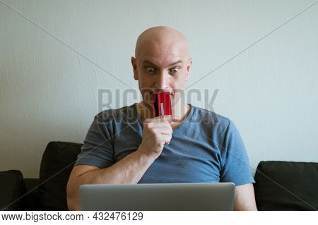 An Adult Bald Man In A Blue T-shirt Is Sitting At Home On The Couch With A Bank Card In His Hand At