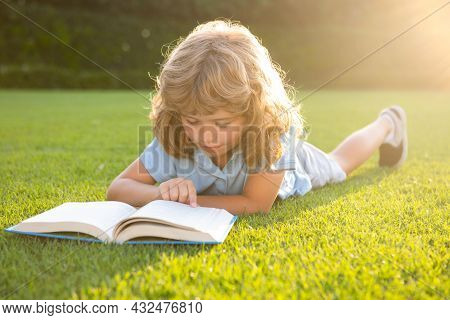 Smart Clever Kids. Child Relax In The Holiday. Kid Read Books On Grass Background.