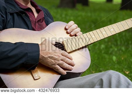 On A Summer Evening, An Adult Romantic Man Sits In A Beautiful Park On The Grass And Holds A Six-str