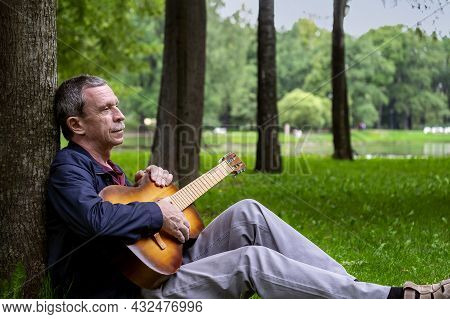 In Summer Evening, Adult Romantic Man Sits In Beautiful Park On Grass, Leaning Against Tree, And Pla