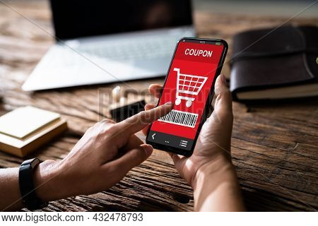 Woman's Hand Holding Mobile Phone With Shopping Coupon