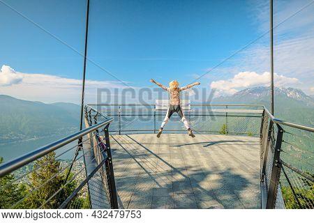 Woman Jumping On Aussichtsplattform Platform Of Cardada-cimetta Mount In Switzerland. Skyline Of Loc