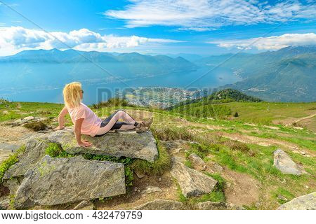 Woman Sitting On Top Of Cardada-cimetta Mount In Switzerland. Swiss Cable Car Aerial View Skyline Of