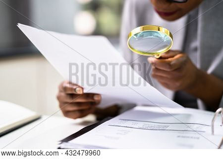 Lawyer Examining Paper Using Magnifier Glass. Tax Fraud Investigation