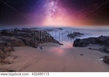 Milky Way Shimmers Over The Ocean Water As It Cascades Over Rocks In Reykjavik, Iceland.
