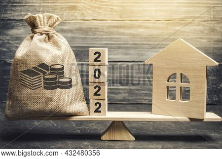 Money Bag 2022 And A Wooden House On The Scales. Real Estate Concept. Family Budget Planning. Invest