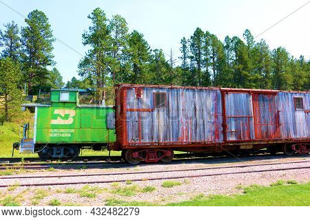 September 8, 2021 In Hill City, Sd:  Vintage Burlington Northern Caboose Besides A Wooden Rail Car O