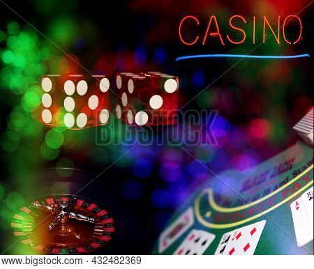 Casino Black Jack Table With Roulette Wheel And Dice. Neon Casino Sign With Bokeh