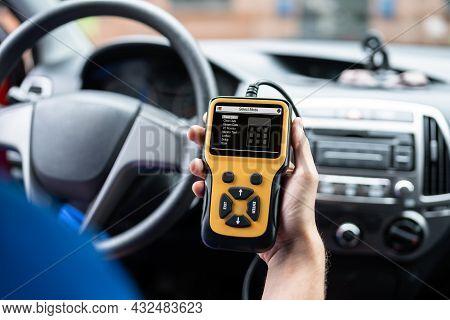 Automobile Service Technician At Car Repair Shop Using Diagnostics Device