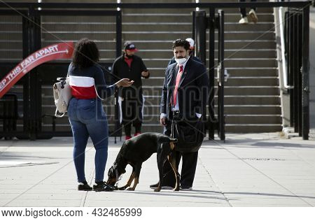 Bronx, New York, Usa - May 20, 2020: Man Wears Mask Against Covid-19 While Speaking To Woman Outdoor