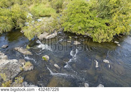 Water Flowing Over Rocks On Shallow Riverbed Amongst Trees, Drone Landscape Aerial