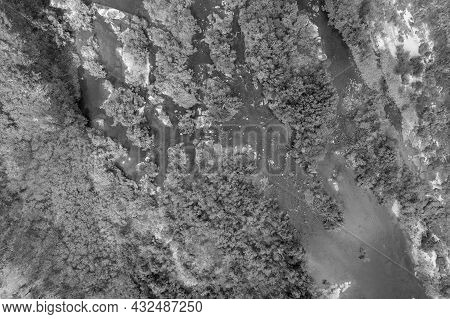 Monotone Of Aerial Landscape Pattern Of A Shallow Riverbed With Water Flowing Between Bushland And R