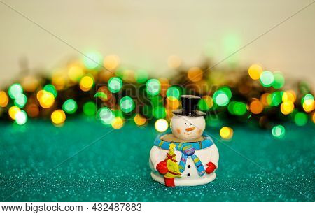 Christmas Card Decorated With Bokeh And Lights. Snowman With Bokeh Christmas Lights In The Backgroun
