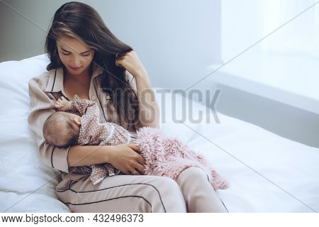 The Woman Is Breastfeeding The Baby. Young Mom Feeds The Baby. High Quality Photo