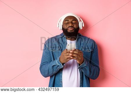 Delighted Black Man Enjoying Awesome Music, Listening Songs In Headphones And Holding Smartphone, Lo