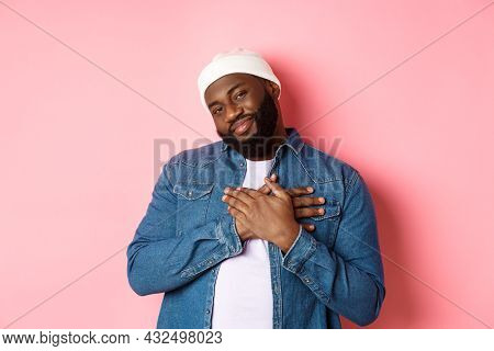 Thankful And Touched Black Guy Saying Thank You, Smiling Adorable And Holding Hands On Heart, Apprec