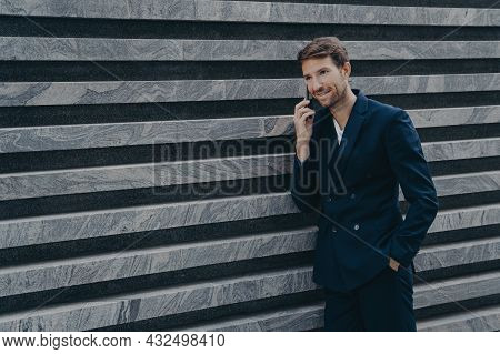Unshaven Male Corporate Worker Dressed In Formal Black Suit Keeps Hand In Pocket Has Telephone Conve