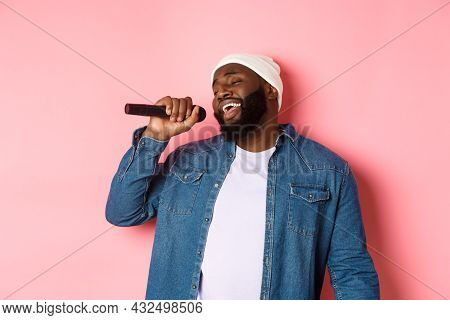 Handsome Black Man In Beanie And Denim Shirt Singing Karaoke, Holding Microphone, Standing Over Pink