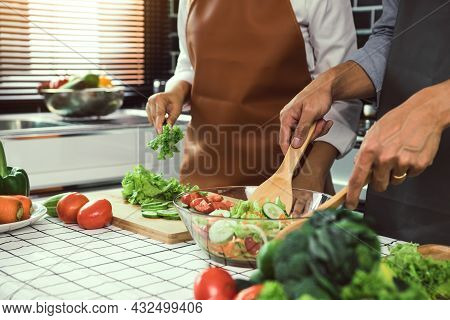 Asian Couple Enjoying Cooking Vegetable Salad In The Kitchen.