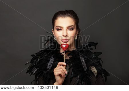 Valentine's Day. Attractive Woman Brunette Holding Red Heart Near Her Lips On Black Portrait