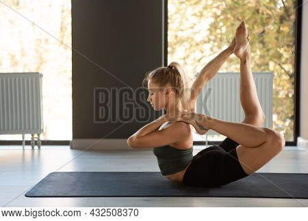 Yoga Master. Portrait Of Young Slim Sportive Woman In Sportswear Doing Exercise On Sports Mat At Yog