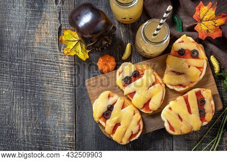 Halloween Party Food. Halloween Mummies Mini Pizzas On A Wooden Table. Top View Flat Lay Background.