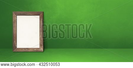 Wooden Picture Frame Leaning On A Green Wall. Blank Mockup Template. Horizontal Banner