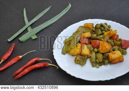 Flat Lay Of Matar Paneer Mix Veg Recipe (indian Food) And Red Chillies Over Black Background