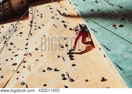 One Caucasian Man Professional Rock Climber Workouts On Climbing Wall At Training Center In Sunny Da