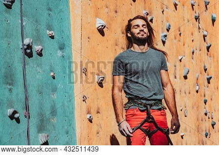 Portrait Of Caucasian Man Professional Rock Climber Standing At Front Of Climbing Wall At Training C