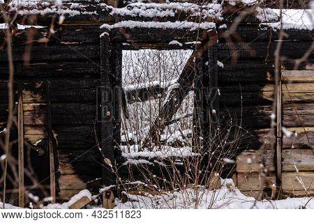 Old Abandoned House Burnt Building In Snow. Charred Wooden Walls And Window Are All What Is Left Fro