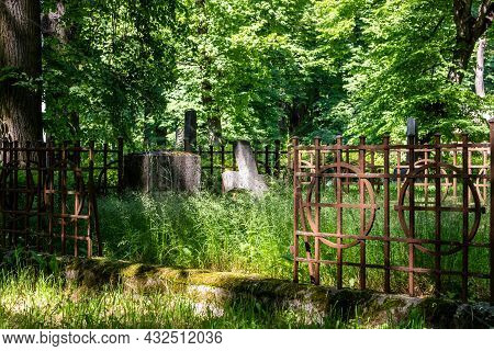 Churchyard Old Burial Ground And Fence In Graveyard Surrounded With Green Trees. Vintage Grave With