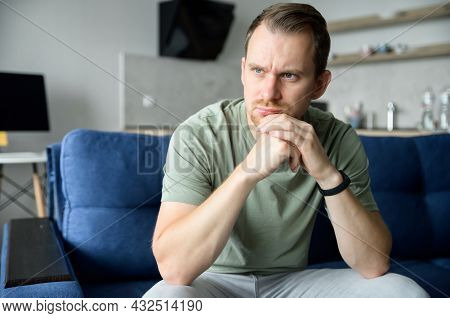 Worried Guy Sits On The Sofa Alone And Looks Away Lost In Thoughts, Upset Young Man Feels Lonely, Ha