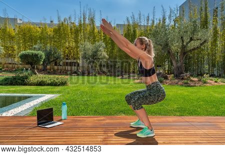 Athletic European Girl Doing Squats Outside In The Park With An Online Fitness Instructor.