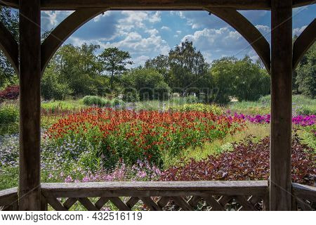Painterly Image Of Beautiful Brightly Coloured Flowers Framed By A Gazebo Summer Landscape. Trees An