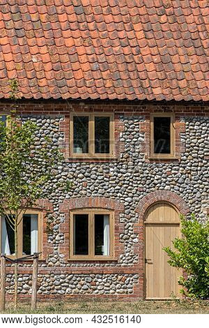 Traditional Flint Pebble Faced Cottage In Rural Norfolk Uk. Close-up Of A Beautifully Restored Old F