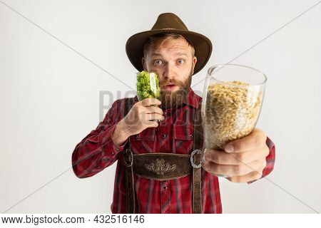 Young Bearded Man In Hat And Traditional Bavarian Costume Holding Beer Glasses Filled With Wild Hot