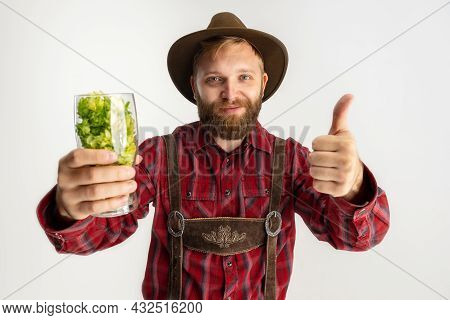 Happy Smiling Man Dressed In Traditional Bavarian Costume Holding Beer Glasses Filled With Wild Hot