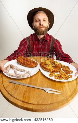 Top View Of Young Bearded Man, Waiter In Traditional Bavarian Costume Holding Round Wooden Tray With