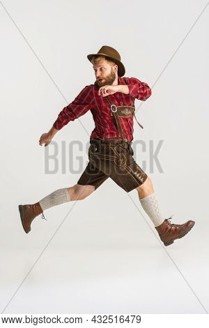 Full-length Portrait Of Bearded Man In Hat And Traditional Bavarian Costume Running Away Isolated Ov