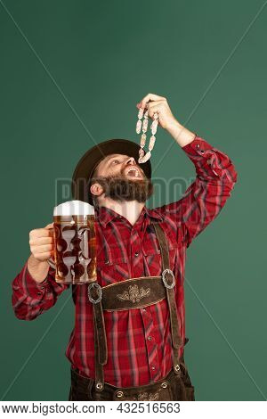 Portrait Of Bearded Man In Traditional Bavarian Costume With Sausages Having Fun Isolated Over Green