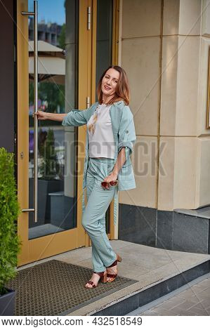 A Woman In A Green Suit At The Door Of A Cafe