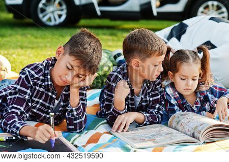 Family Spending Time Together. Three Kids Outdoor In Picnic Blanket.
