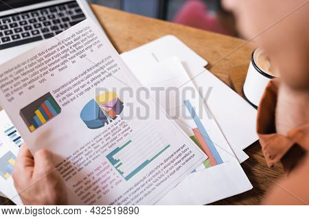 Partial View Of Young Man Holding Charts And Graphs Near Laptop In Cafe