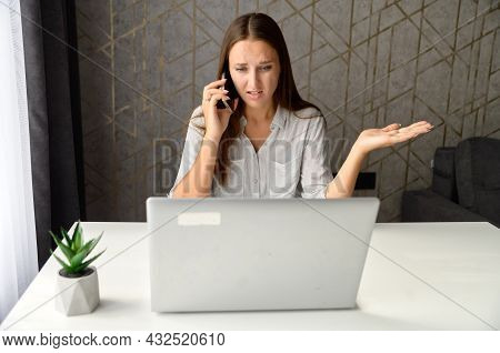 Irritated Woman Talking On The Phone While Sitting At The Desk At Home Office And Using Laptop. Upse