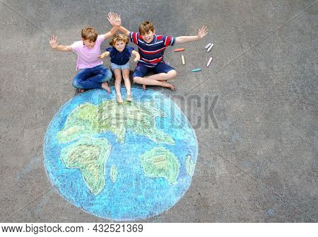 Little Preschool Girl And Two School Kids Boys With Earth Globe Painting With Colorful Chalks On Gro