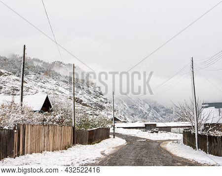 Russian Rural Village Chemal In The Snow. The Road Going Into The Distance To The Altai Mountains Al