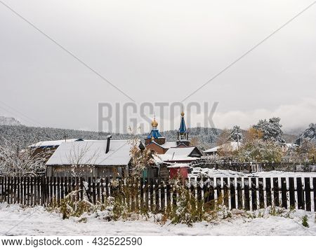 Russian Rural Village Chemal In The Snow. A Church With A Blue Roof And Golden Domes Against The Bac